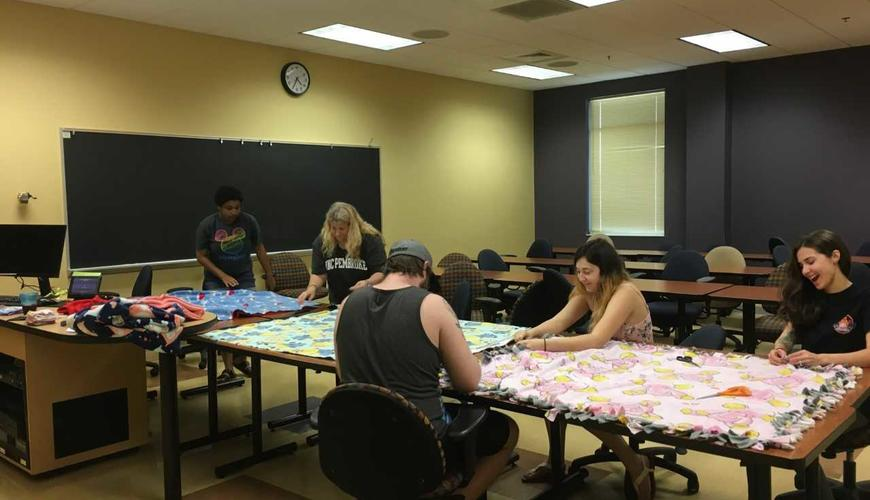 Psi Chi students volunteering to make blankets for the Child Advocacy Center in Fayetteville. We donated 10 blankets and had a lot of fun making them! :-) One of the pictures was taken at the Child Advocacy Center once Babs dropped the blankets off.