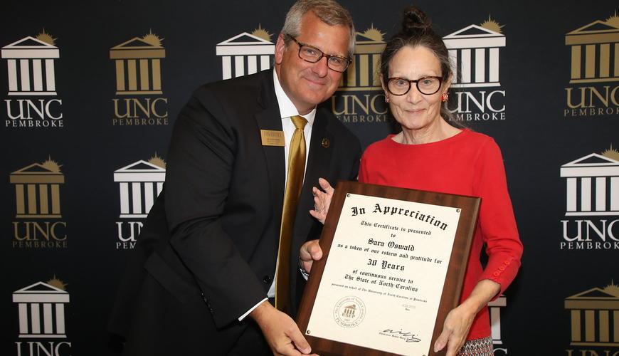 Provost David Ward congratulates Sara Oswald on her 30 years of service to UNCP.