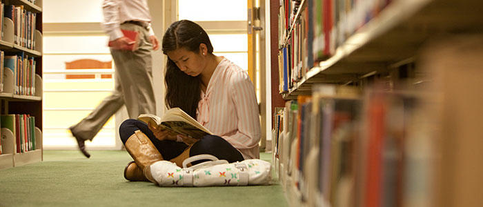 Girl reading a book in the library
