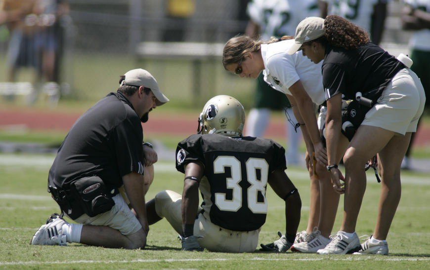 Athletic trainer and AT students evaluating an injured football player.