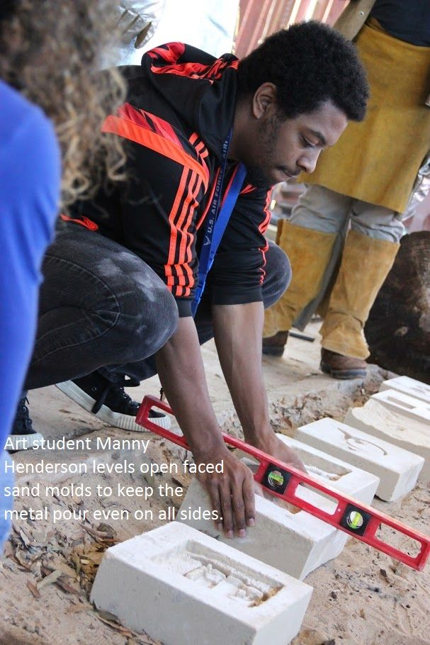 Art Student Manny Henderson levels open faced sand molds to keep the metal pour even on all sides