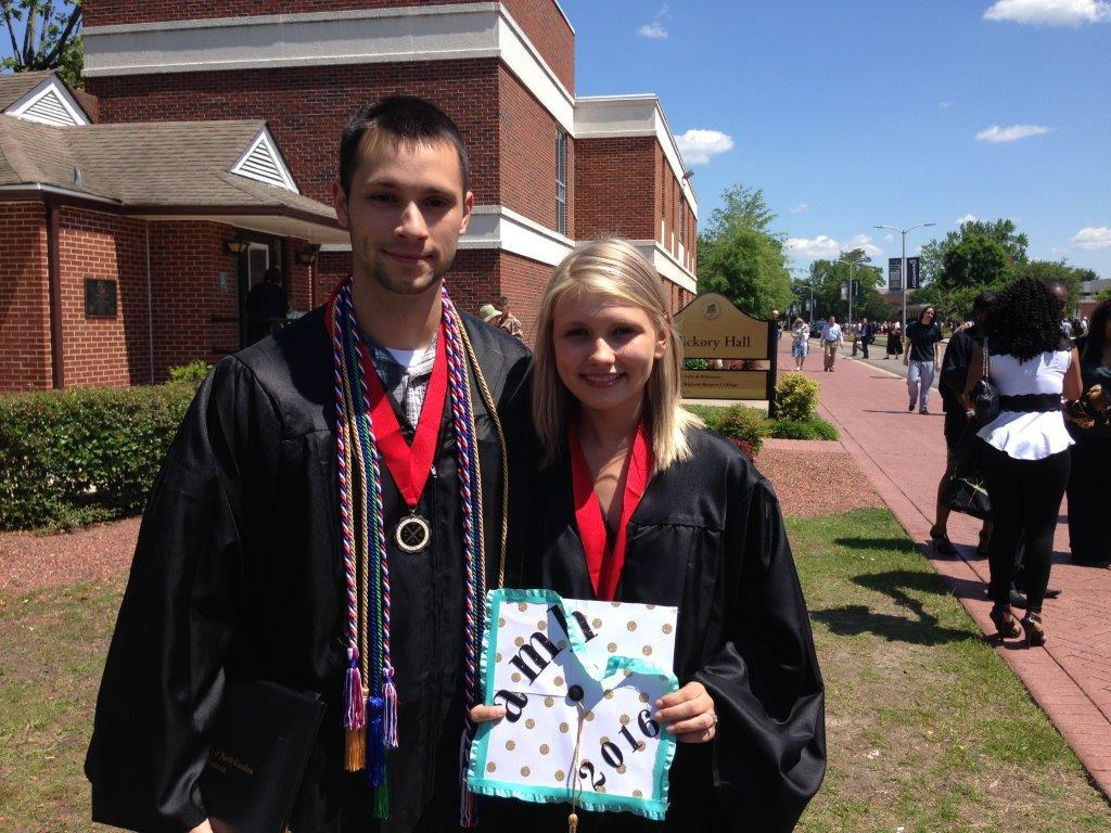 English majors Micah Simpson and Amber Hester pose with their regalia