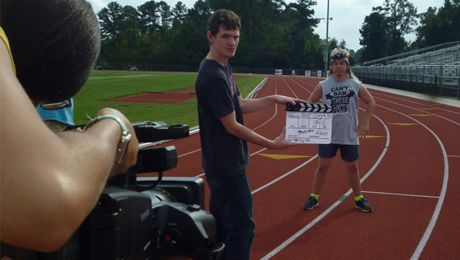 A student marks a take of a student video production.