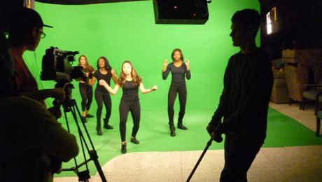 Students operate a dolly rig while dancers perform on the greenscreen set.