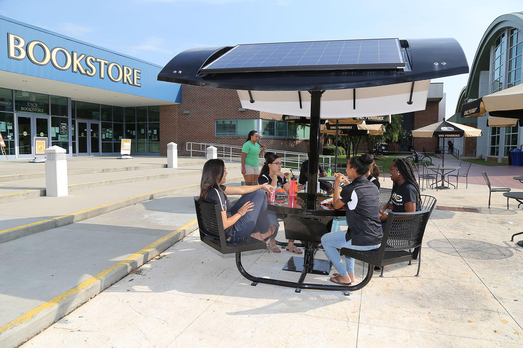 Student Green Fee funds enabled the campus to acquire a solar table, which students enjoy