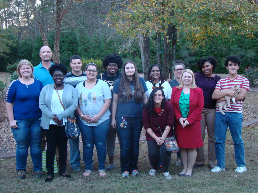 RISE Fellows and staff standing on a lawn, with trees in the background, facing the camera for a group picture.