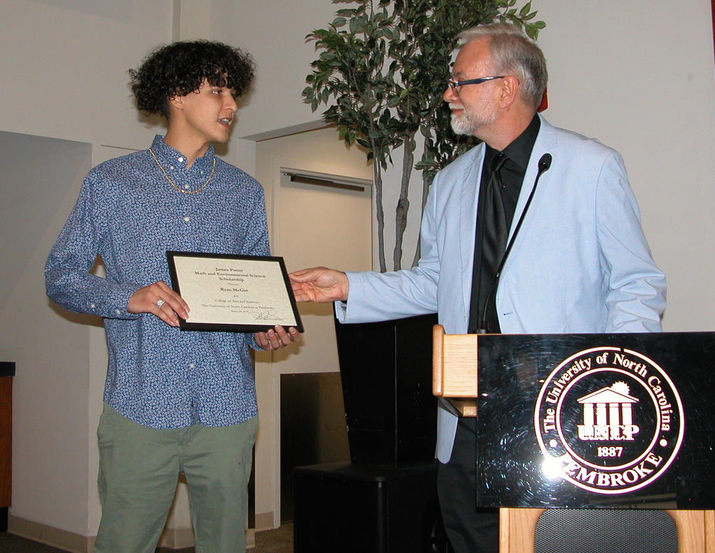 Ryan McGirt receiving the James Porter Math and Environmental Science Scholarship from Dr. Richard Gay