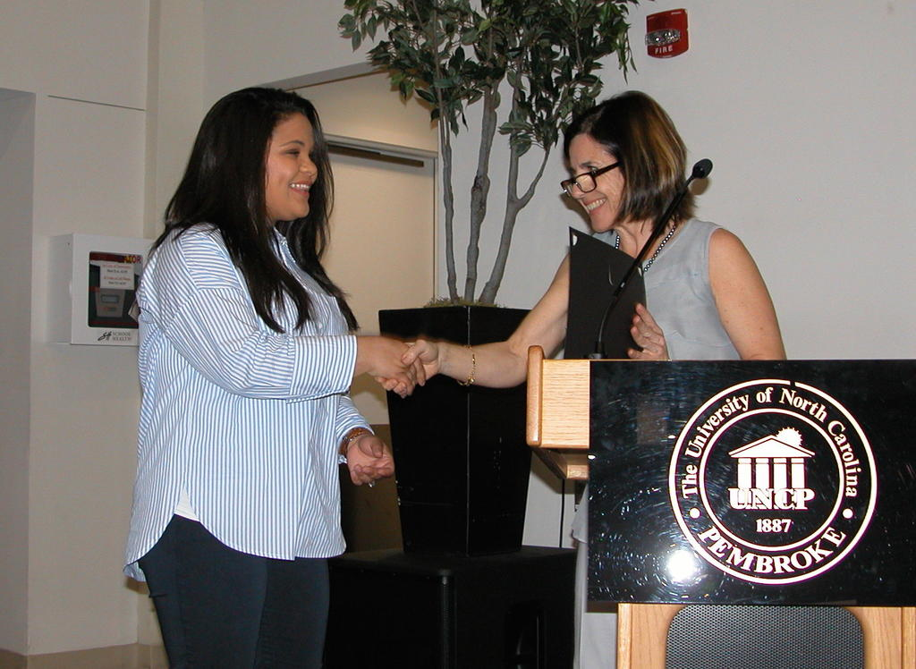 Sarah Locklear receiving the Environmental Science Sustainable Agriculture Scholarship from Dr. Maria Santisteban