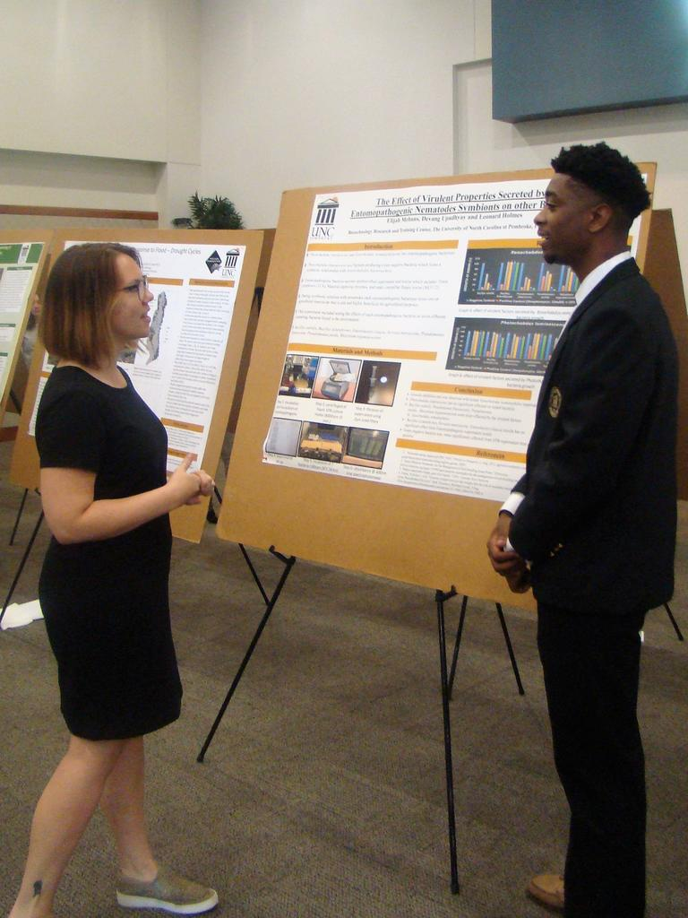 Dr. Joanna Cooper chatting with Elijah Mebans about his research