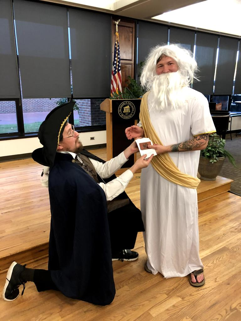 Dr. Michael Berntsen (left) presents Kody Peterson (right) with an award for best student costume at the 2018 Dead Author Night.