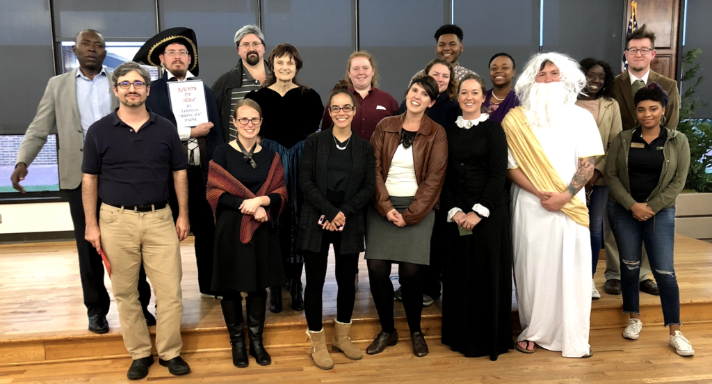 Faculty and students pose for a photo after reading works from dead authors on Dead Authors Night 2018.