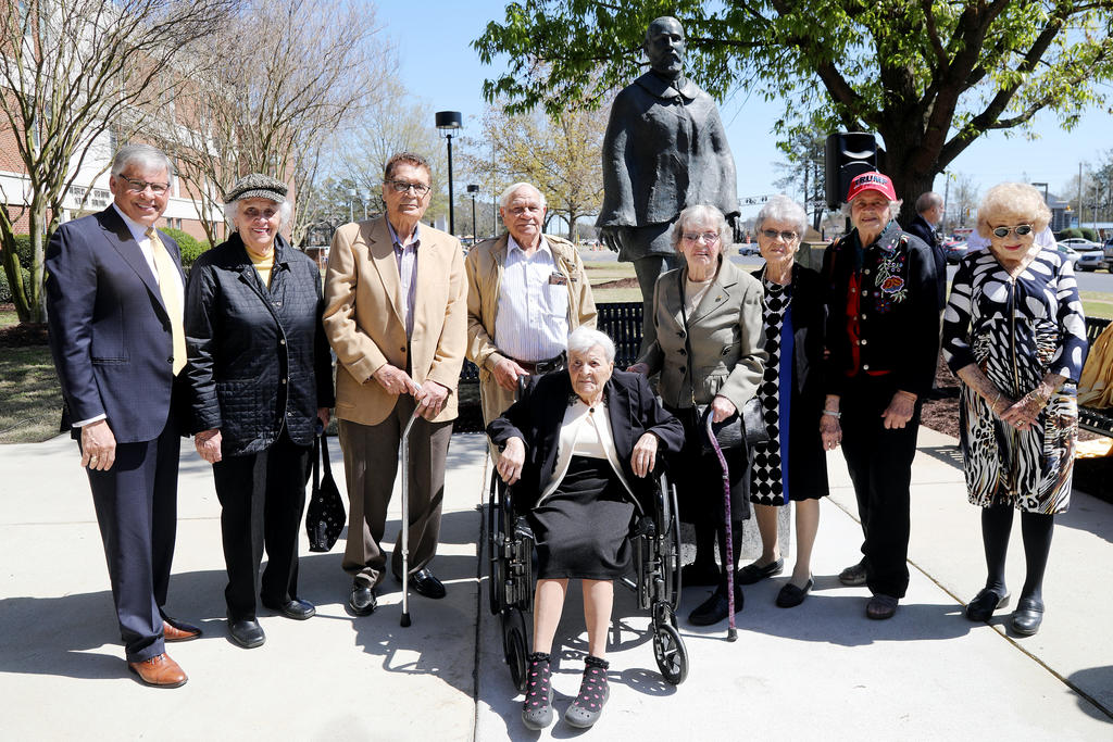 Chancellor Robin Gary Cummings (left), poses in front of the Hamilton McMillan statue with alumni Dorothy Blue, James C. Dial, Josephus Locklear, Cattie Mae Hunt (seated), Josephine Ransom and her twin sister Catherine Locklear, Bernice Brooks Lowry and Doris Hall