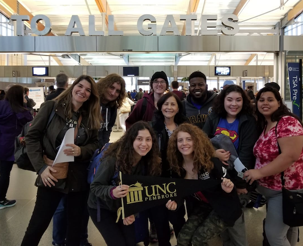 Foreign Languages Program faculty and students pose for a picture at the airport during a spring break trip to South America. Pictured here (from left to right) are Dr. Ana Cecilia Lara, Holden Jolley, Sarah Rodriquez, Antonia Uchytil, Milagros López-Fred, Ignayara Hernandez, Zachary McDowell, Angela Dial, and Lena Paz.