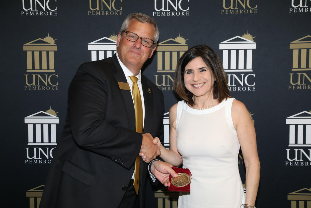 Provost David Ward congratulates Dr. Maria Santisteban for her promotion to full professor