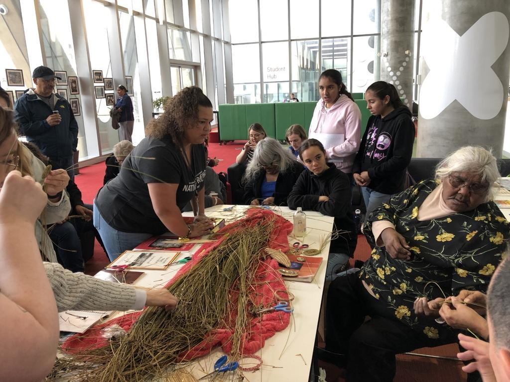 Regan Scott (leaning on table) watching weaving instruction by Ngarrindjeri elders during a weaving workshop.