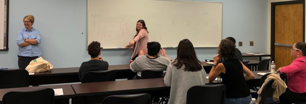 Dr. Wendy Pearce Miller (left) moderates a Pictionary match during the English majors meeting in October 2019.