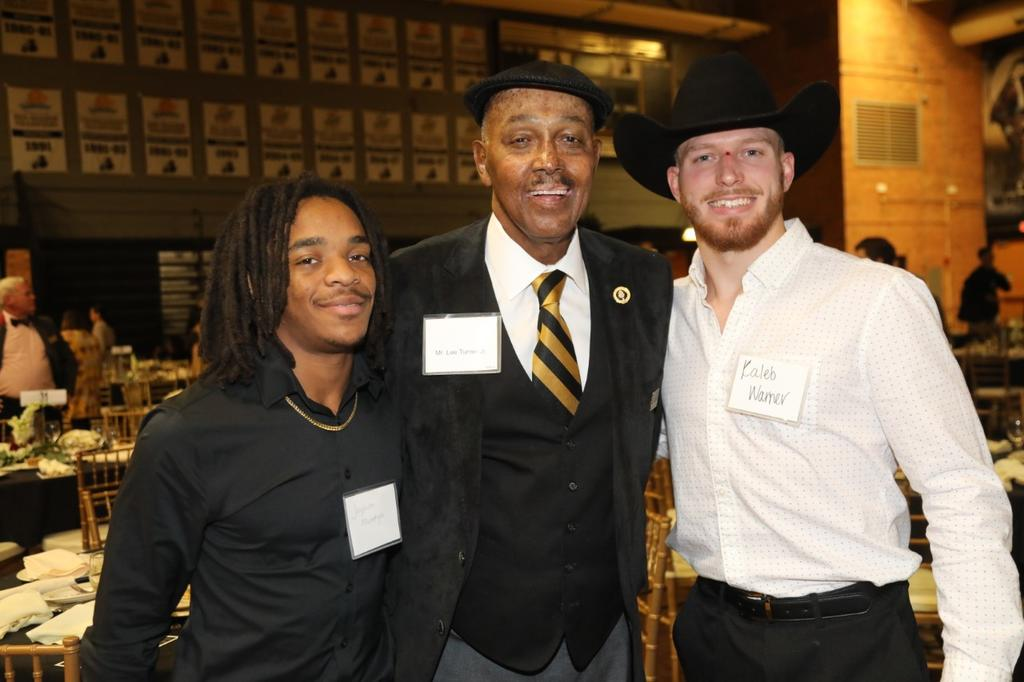 Jayquon McEntryre and Kaleb Warner pose with longtime UNCP supporter Lee Turner