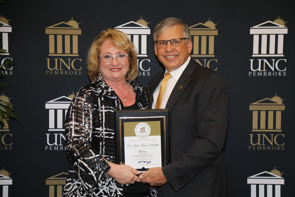 Chancellor Robin Gary Cummings presents Dr. Lisa Schaeffer, vice chancellor for Student Affairs, with a plaque recognizing 35 years of service to the university