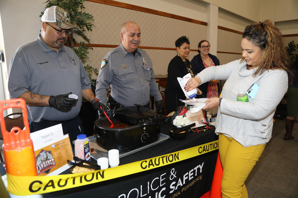 Members of the Law Dawgs team (Police & Public Safety) serve up a sample of their secret recipe at the annual Staff & Faculty Chili Cook-Off