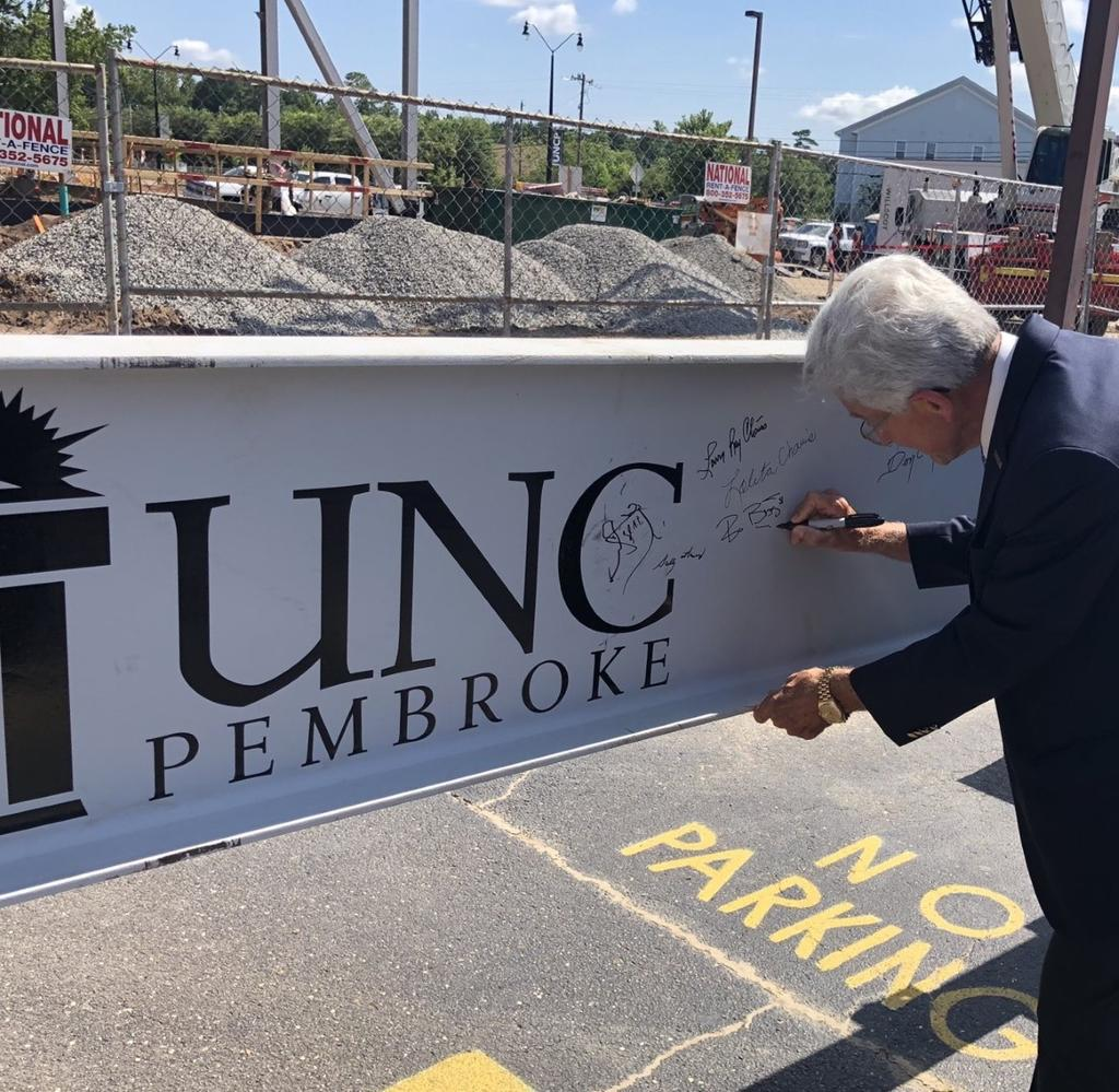 Bo Biggs, chairman of the Golden LEAF Foundation, signs the final beam at the topping out ceremony on July 23, 2020