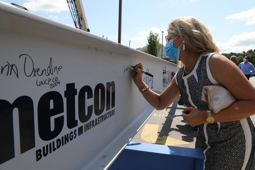 Jodi Willis, daughter of Mary and the late Wyatt Upchurch, signs the final beam during at the topping out ceremony on July 23, 20202